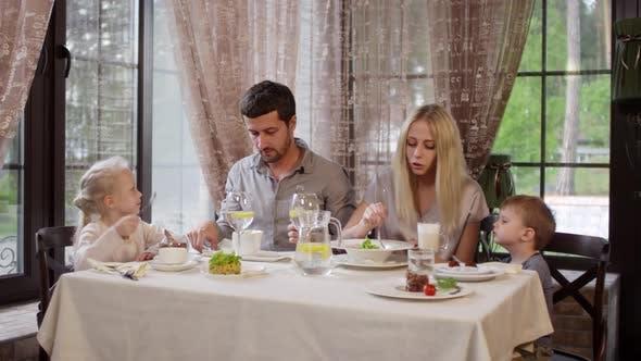 Thumbnail for Family of Four Eating in Restaurant