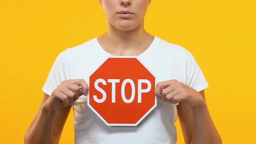 Serious Woman Holding Stop Sign