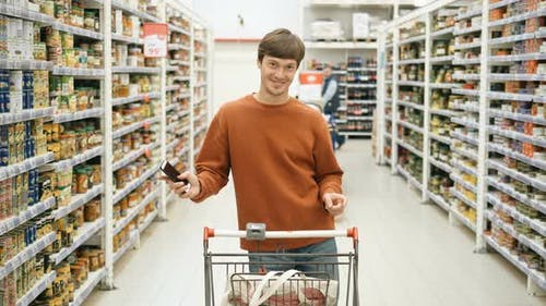 Pretty Guy with a Phone and a Food Basket Dancing in the Supermarket