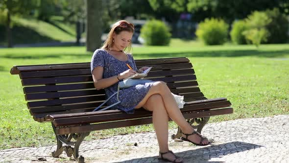 Thumbnail for Young Girl Sitting at the Bench in a Park and Making Notes