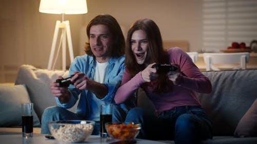 Young Excited Married Couple Playing Video Games with Joysticks Woman Winning Man Feeling Sad Slow
