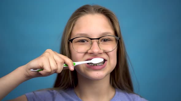 Thumbnail for Girl with Braces Brush Her Teeth with a Toothbrush Closeup. A Girl with Colored Braces on Her Teeth