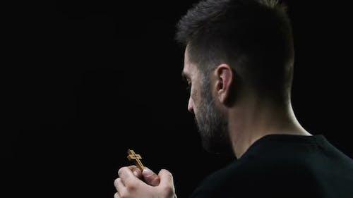 Mann hält Kreuz und betet vor schwarzem Hintergrund, Christian Religion
