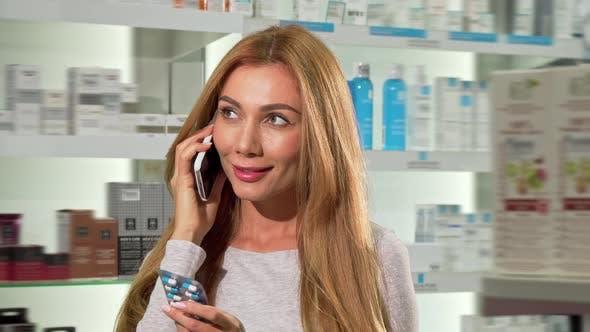 Thumbnail for Attraktive Frau sprechen am Telefon, Einkaufen bei Drogerie