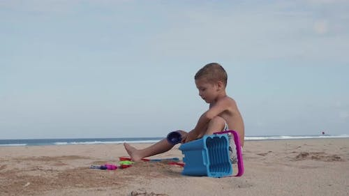 Boy Sitting on Sand and Playing Toys