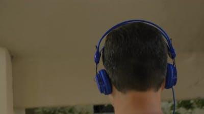 Man in headphones walking downstairs