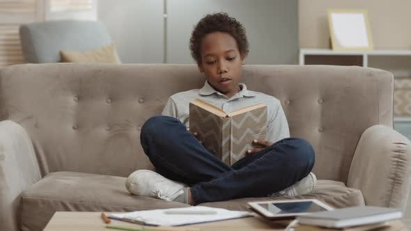 African Boy Reading Book on Couch