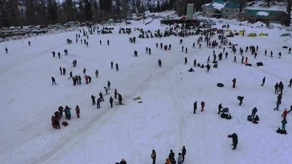 Thumbnail for Aerial Slow Moving Shot of a Crowd Enjoying Themself in Snow Adventure Valley in Solang , Himachal