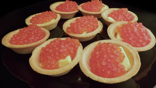 Red Caviar Is Put with a Spoon on Tartlets. Preparation of Snacks with Red Caviar. Top View