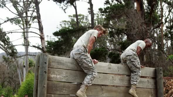 Thumbnail for Military people climbing hurdles during obstacle course 4k