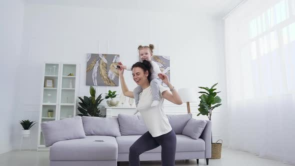 Woman Doing Sit-Ups with Her Cute Funny Little Daughter which Sitting on Her Neck at Home