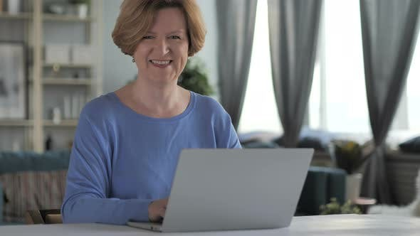Cover Image for Smiling Old Senior Woman Looking at Camera while Working on Laptop