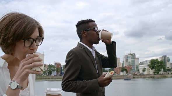 Thumbnail for Business Partners Eating Wraps and Having Coffee during Walk