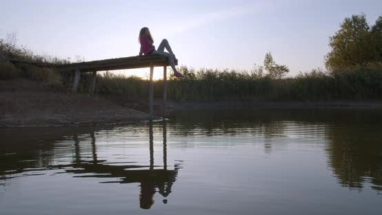 Thumbnail for Woman Relaxes By the Lake Sitting on the Edge of a Wooden Jetty , Swing Legs on the Sunset