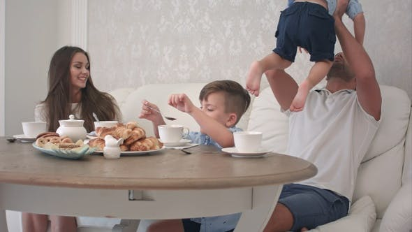 Thumbnail for Happy family playing together while having breakfast at