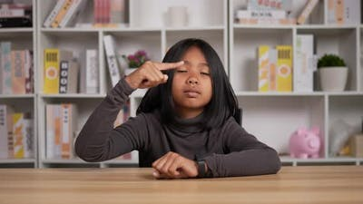 Girl sitting at desk and pointing on watch