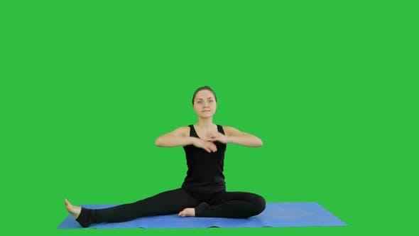 Thumbnail for Young Woman Stretching Her Legs While Doing Yoga Practice on a Green Screen, Chroma Key