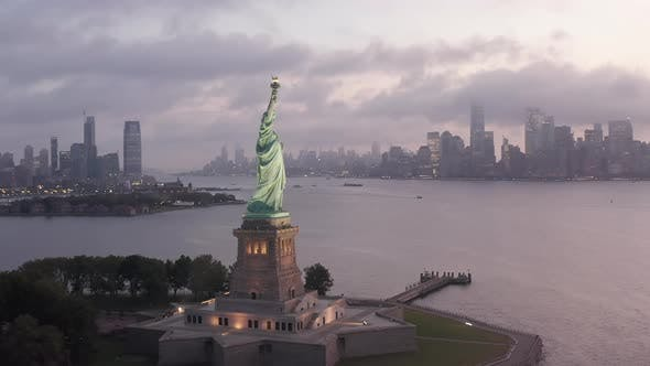 Cover Image for Circling Statue of Liberty Illuminated in Early Morning Light with Foggy New York City