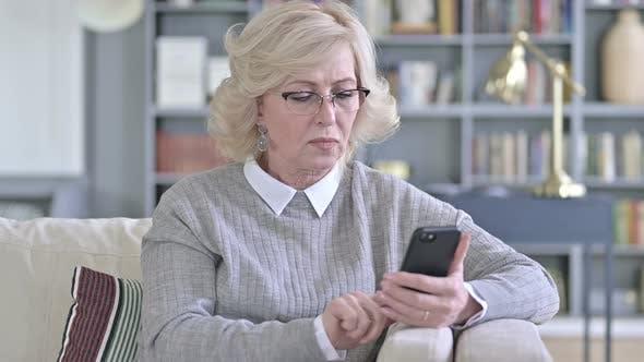 Thumbnail for Sad Old Woman Facing Loss on Smartphone