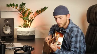Guitarist playing acoustic guitar in cozy living room.