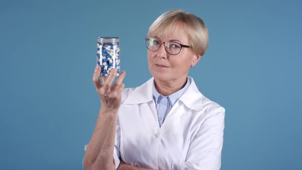 Thumbnail for Middle-Aged Female Doctor Holding Bottle of Pills