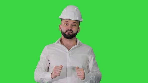 Engineer in a White Helmet Explaining Something To Camera on a Green Screen Chroma Key