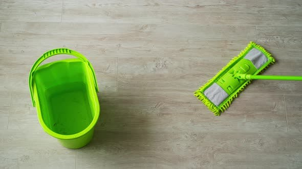 Green bucket and mop on the parquet floor