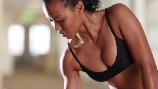 Thumbnail for Strong mixed race asian woman doing bicep curls at the gym