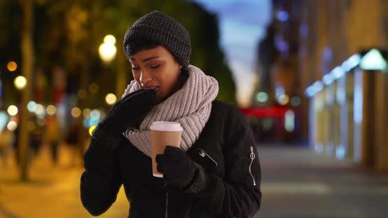 Thumbnail for Pretty black woman with warm cup of coffee using smartphone outside