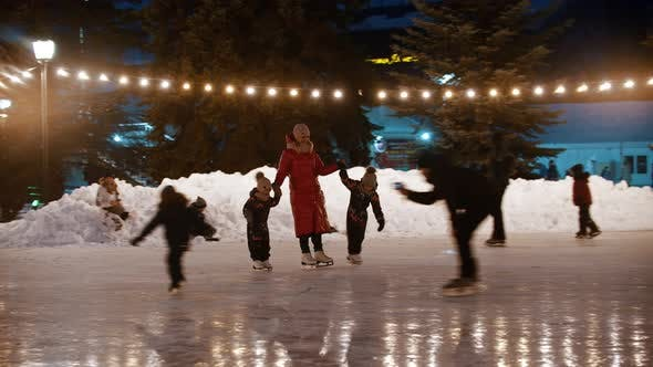 Thumbnail for A Family of Young Mother and Two Kids Skating on the Decorated Ice Rink Holding Their Hands