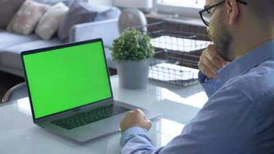 Over the shoulder shot of man working on laptop with green screen display