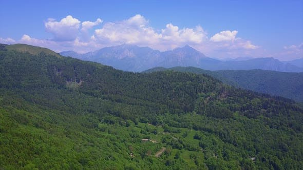 Thumbnail for Aerial Drone Flying Over Mountain Valley Overlooking High Peaks and Hills Covered with Green Forest