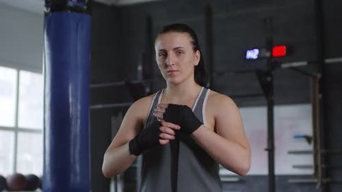 Female Fighter Wrapping Hands for Boxing and Looking at Camera