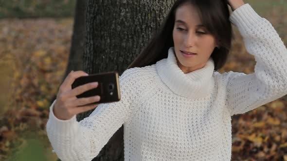 Girl Makes Selfie in the Autumn Park