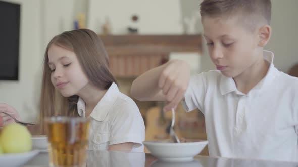 Porträt von Bruder und Schwester Twin Essen nicht lecker Porridge oder Cornflakes zum Frühstück ohne