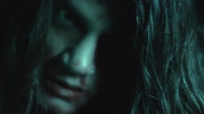 Terrifying creepy zombie woman with white eyes and scary look. Horror style shot