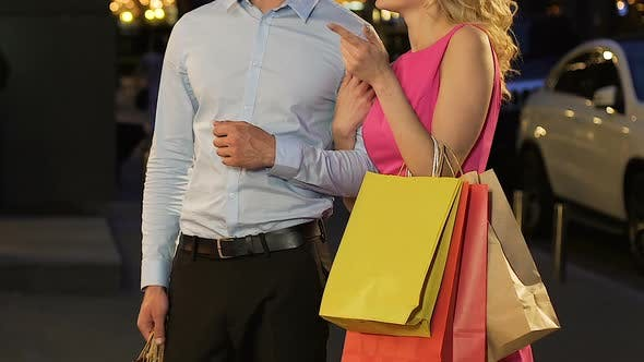 Thumbnail for Couple Standing in Street with Shopping Bags Girl Talking to Guy and Smiling