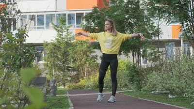 Young Sporty Woman Exercises in an Urban Environment