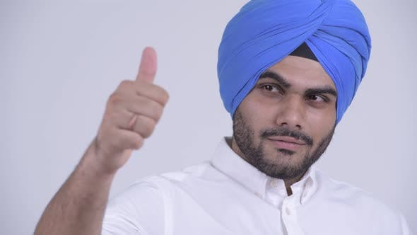 Thumbnail for Face of Happy Young Bearded Indian Sikh Man Thinking and Giving Thumbs Up