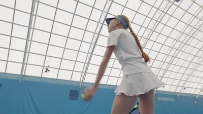 Little Girl Throwing And Hitting Tennis Ball
