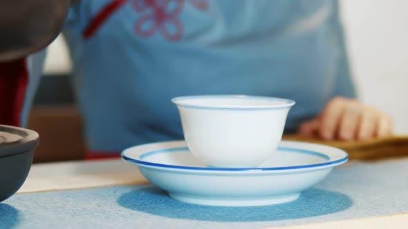 Thumbnail for Rauch aus einer Tasse Tee. Eine Frau gießt kochendes Wasser in eine Tasse bei einer Teezeremonie. Nahaufnahme
