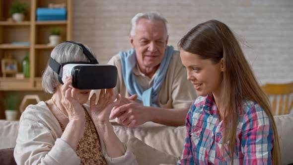Thumbnail for Young Woman Explaining VR Headset to Grandparents