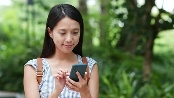 Cover Image for Woman look at cellphone with the background of green plant