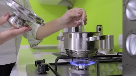 Cover Image for Woman Cooking in a Small Metal Pan on Gas Burner in Kitchen