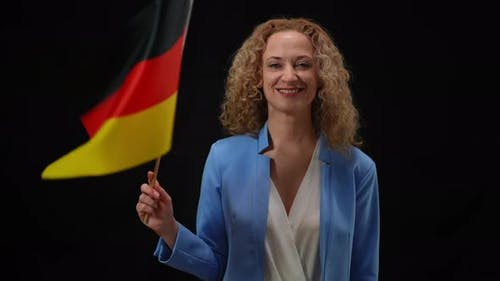 Confident Smiling Elegant Woman Fluttering German Flag Looking at Camera in Camera Flashes at Black