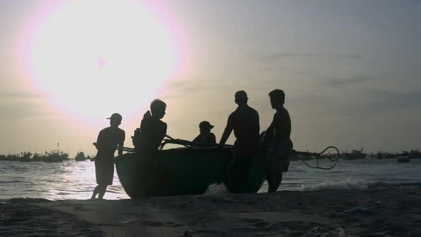Thumbnail for Fishermen Silhouettes Haul Round Boat To Beach at Backlight