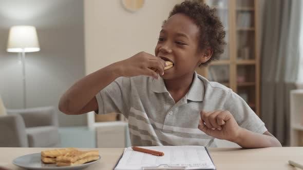 Thumbnail for Kid Snacking on Waffles Doing Homework