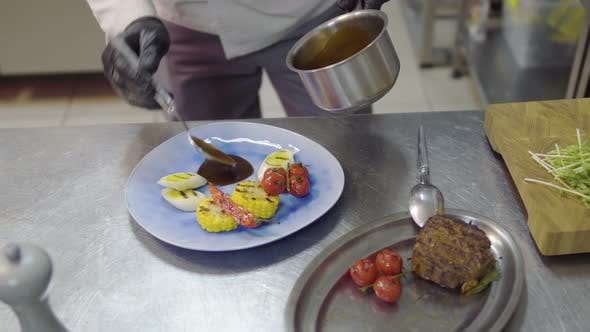 Thumbnail for The Chef Pouring Sauce on the Plate with Grilling Meat, Corn, Cherry Tomatoes, Lemongrass and Chili