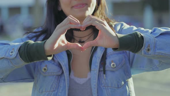 Cover Image for Closeup Shot of Teen Girl Making Heart Shape with Hands