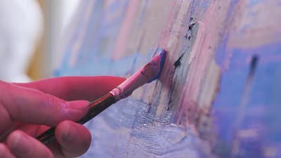 Paint Artist Drawing an Abstract Painting in Blue and Lavender Tones with a Brush and Oil Paints